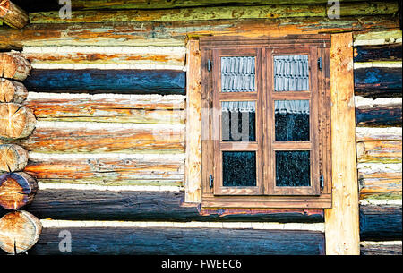Dirty window of an old log cabin with different colored beams. - Stock Photo