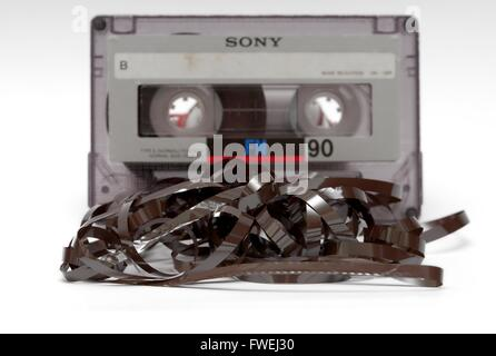 An audio cassette with magnetic tape pulled out. - Stock Photo