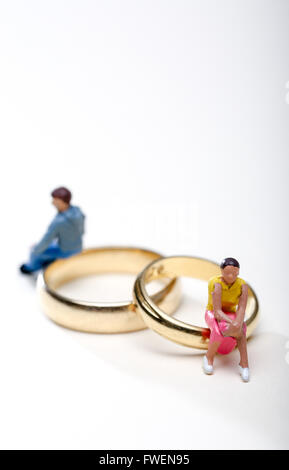 Concept image of a couple sat on wedding rings to illustrate divorce and separation - Stock Photo