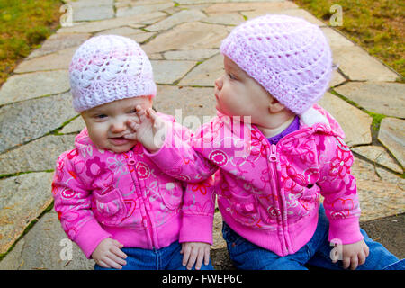 Two twin baby girls sit on a stone walkway wearing pink sweatshirts and beanies. - Stock Photo