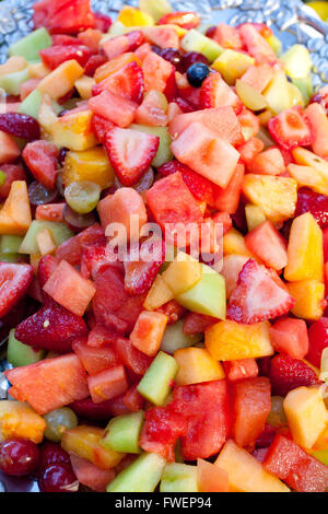 A healthy platter of fruit at a wedding buffet. This image is in color and a vertical composition. It includes strawberries, - Stock Photo