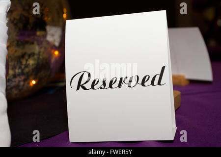 This piece of paper has the word reserved written on it in type letters to indicate for guests not to sit here. - Stock Photo