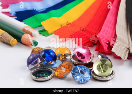 Colorful zippers, pencils and buttons on white background. - Stock Photo