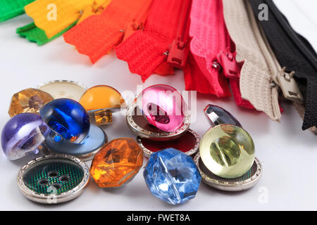 Colorful zippers and buttons on white background. - Stock Photo