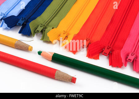Colorful zippers and pencils on white background. - Stock Photo