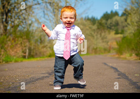 A one year old boy taking some of his first steps outdoors on a path with selective focus while wearing a nice shirt - Stock Photo