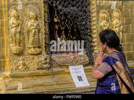 Nepal, Kathmandu, Swayambhunath.  Woman Praying in front of Buddhist Shrine. - Stock Photo