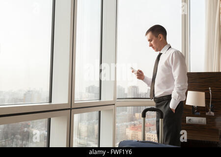Young traveler businessman wearing white shirt and necktie making call after arriving in the hotel room with his - Stock Photo