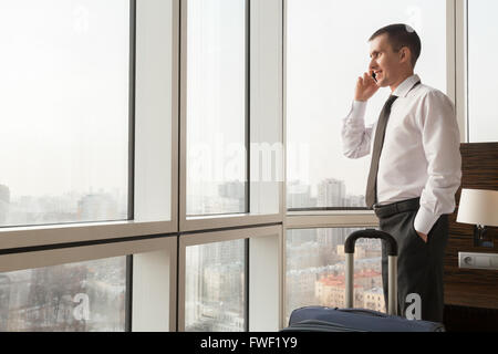 Young happy traveler businessman wearing white shirt and necktie making call after arriving in the hotel room with - Stock Photo