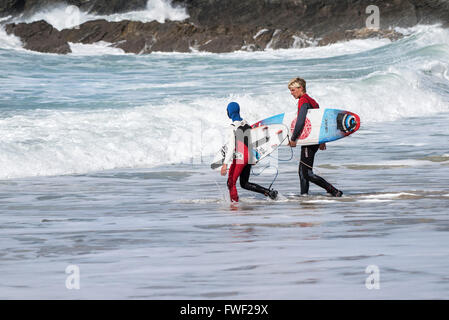 Two young surfers walk into the sea at Fistral Beach in Newquay, Cornwall - Stock Photo