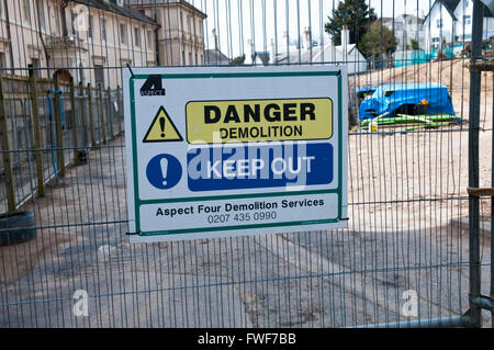 Sign on a building site saying Danger Demolition Keep Out - Stock Photo