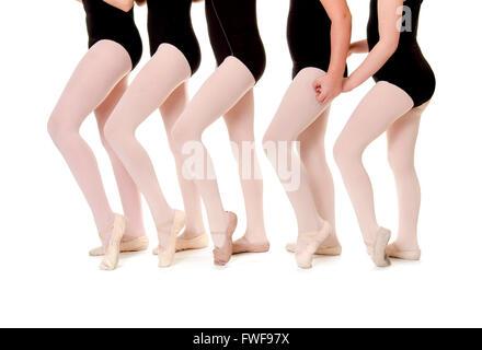 Five Preteen Ballet Student Legs and bodies lineup in Unison wearing school uniform - Stock Photo