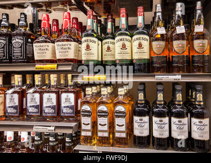 bottles of alcohol on the shelves of a liquor store - Stock Photo