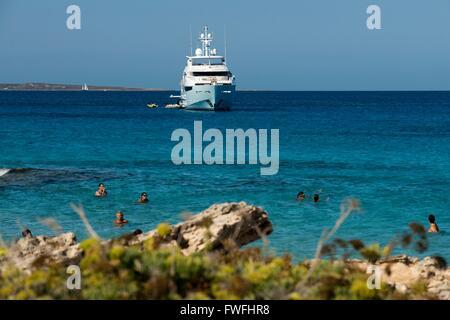 People bathing. Es Pujols beach, Formentera. Luxury yacht in turquoise water in Es Pujols beach Formentera mediterranean - Stock Photo