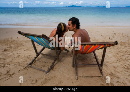 Couple lovers kissing in a hammock on the beach. Phi Phi don. Relax Beach. Phak Nam Bay. Thailand. Asia. Phi Phi - Stock Photo