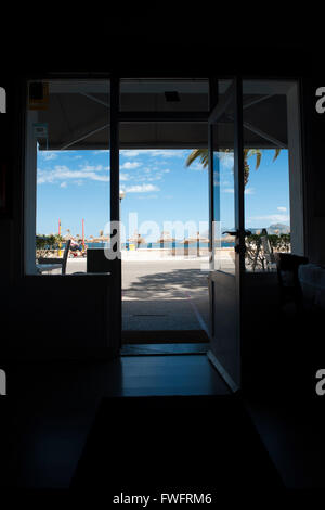 The view of Beach Parasols and Sun Loungers and a blue sky at Pollenca Beach the interior of a restaurant  in Port - Stock Photo