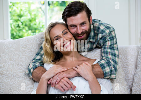 Husband embracing wife from behind against window - Stock Photo