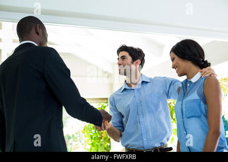 Real estate agent giving house keys to the couple - Stock Photo