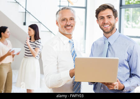 Two businessmen are smiling, posing and holding a laptop - Stock Photo