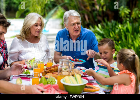 Granparents having breakfast with family at yard - Stock Photo