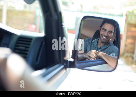 Handsome man sitting in car on mirror - Stock Photo