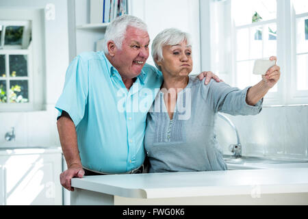 Retired couple making faces - Stock Photo