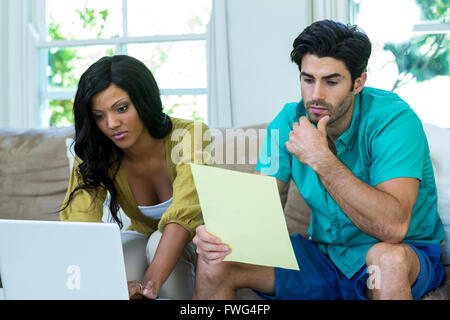 Thoughtful man checking at bills while woman using laptop - Stock Photo
