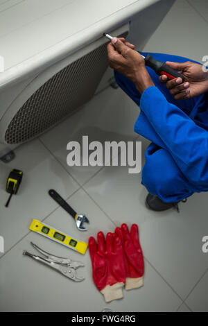 Handyman testing air conditioner with screwdriver - Stock Photo