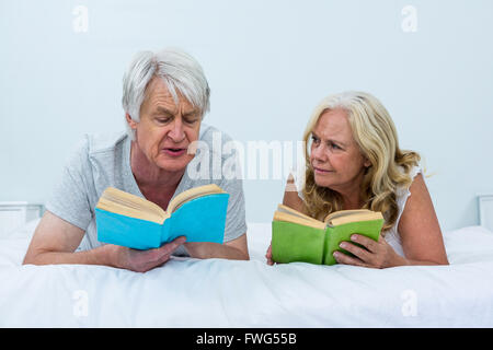 Senior couple reading books while relaxing on bed - Stock Photo