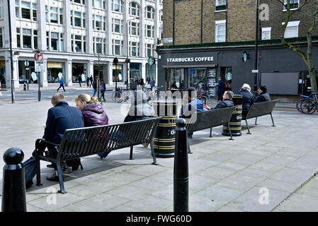 People sitting on benches in public open space off Tottenham Court Road, London Borough of Camden England Britain - Stock Photo