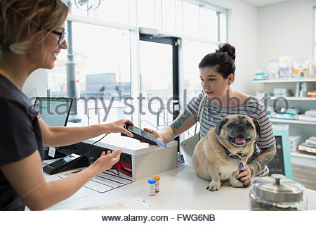 Woman with dog using credit card machine veterinarian - Stock Photo