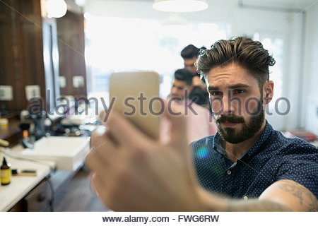 Bearded man taking selfie in barber shop - Stock Photo