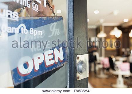 Open sign hanging in barber shop door - Stock Photo
