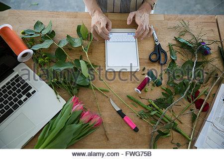 Overhead view florist using digital tablet - Stock Photo
