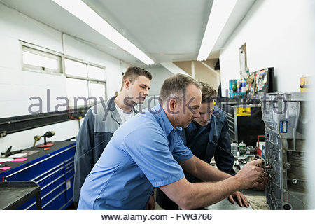 Mechanics examining part in auto repair shop - Stock Photo