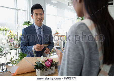 Man paying florist for bouquet in flower shop - Stock Photo