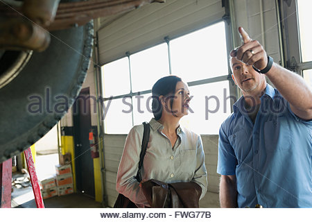 Mechanic explaining to customer in auto repair shop - Stock Photo