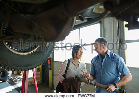 Mechanic discussing part with customer auto repair shop - Stock Photo