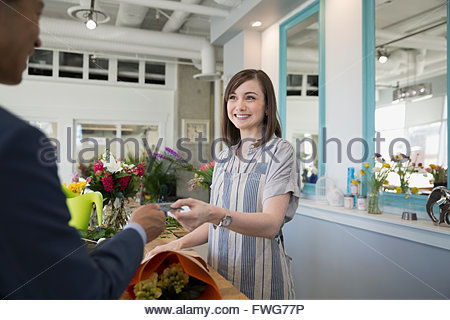 Man paying florist with credit card flower shop - Stock Photo