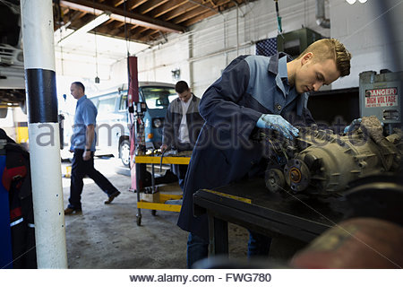 Mechanic fixing engine in auto repair shop - Stock Photo
