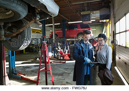 Mechanic with clipboard explaining customer auto repair shop - Stock Photo