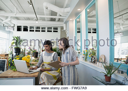 Florists working at laptop in flower shop - Stock Photo