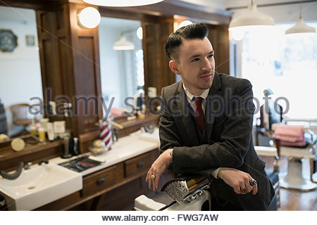 Confident barber wearing suit in barber shop - Stock Photo