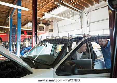Mechanics with laptop talking in auto repair shop - Stock Photo