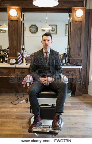 Portrait confident barber wearing suit barber shop chair - Stock Photo