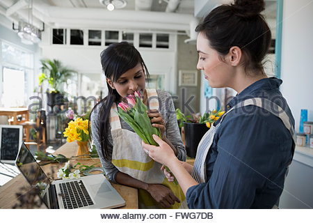 Florists smelling tulips in flower shop - Stock Photo