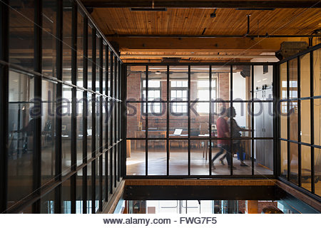Women walking along elevated walkway industrial office - Stock Photo