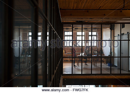 Designers working in industrial office in distance - Stock Photo