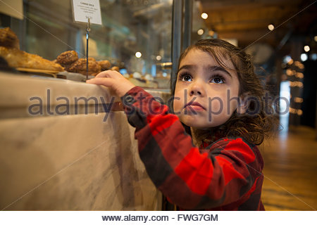 Cute girl looking up at bakery display case - Stock Photo