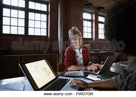 Smiling designers working at laptops in office - Stock Photo